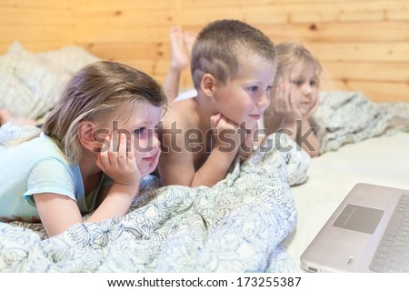 Lovely kids looking at computer monitor while laying in bed - stock photo