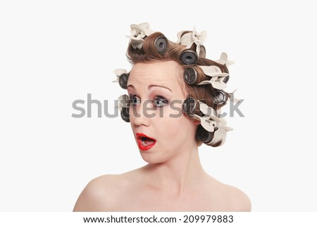 Lovely Lady with Hair Curlers Looking Surprised against light background. / Lovely Lady with Hair Curlers Looking Surprised - stock photo