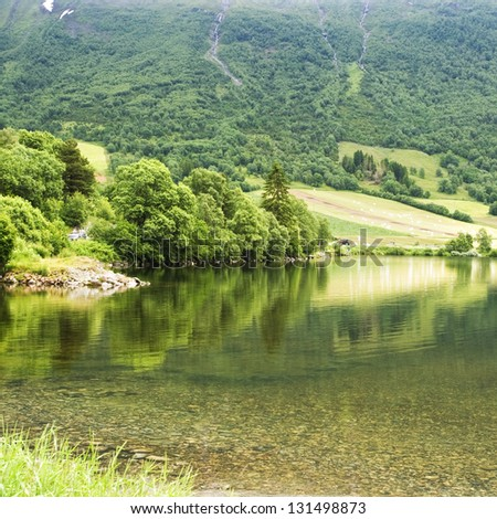 Lovely lake in Norway forest hills - stock photo