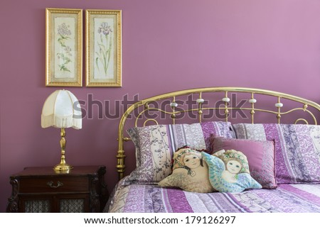 Lovely lavender bedroom interior with brass headboard and furnishings - stock photo