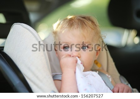 Lovely little baby girl sitting in the car in a child seat locked with safety belt - stock photo