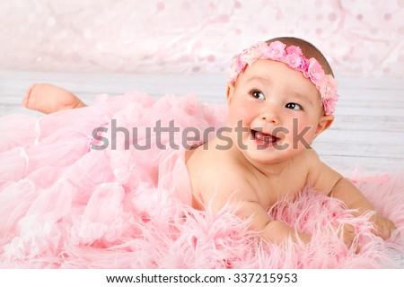 Lovely little baby girl wearing tutu skirt and floral headband - stock photo