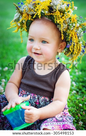 Lovely little baby girl with daisy wreath on her head - stock photo