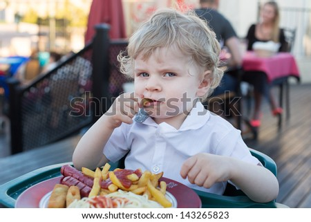 Lovely little boy eating french fries in summer, outdoors - stock photo
