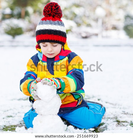 Lovely little boy in colorful clothes making a snowman, playing and having fun with snow, outdoors  on cold day. Active outoors leisure with children in winter. - stock photo