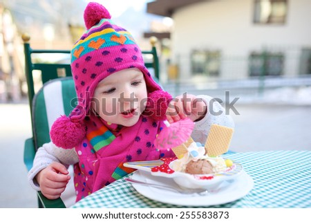 Lovely little child, adorable toddler girl wearing colorful pink hat, eating delicious ice cream in outdoors street cafe enjoying weekend city trip with family - stock photo