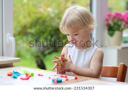 Lovely little child, blonde curly toddler girl using her imagination creating make-believe cookies from play dough compound sitting indoors in bright room with big garden view window - stock photo