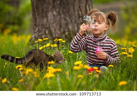Lovely little girl and a cat, blowing soap bubbles - stock photo