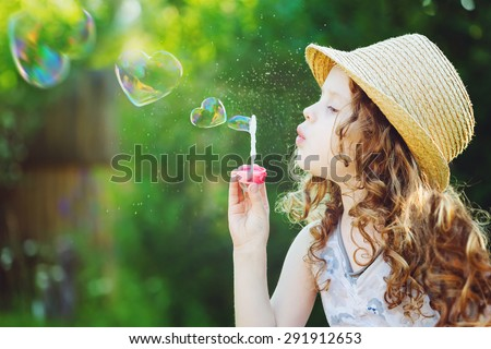 Lovely little girl blowing soap bubbles in a heart shape. Happy childhood concept. Background toned in instagram filter. - stock photo