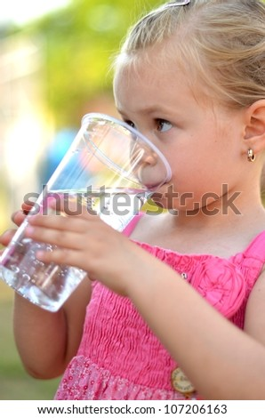 Lovely little girl drinking water - stock photo