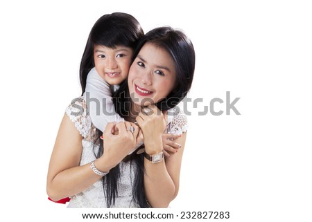 Lovely little girl hugging her mother from the back while smiling at camera in studio - stock photo