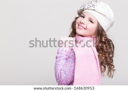 Lovely little girl in winter knitted hat pink scarf gloves and colorful cozy sweater. Kid fashion. Happy baby girl in woolen accessories at studio. Space and white background. - stock photo