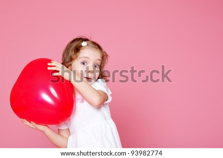 Lovely little girl playing with red heart shaped balloon - stock photo