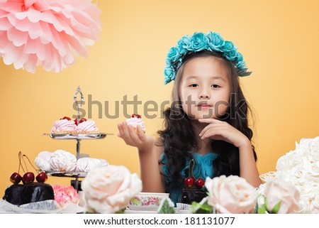 Lovely little girl posing while drinking tea - stock photo