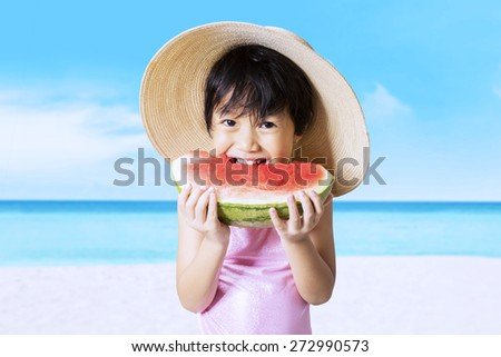 Lovely little girl wearing a hat on the beach while eating a fresh watermelon - stock photo