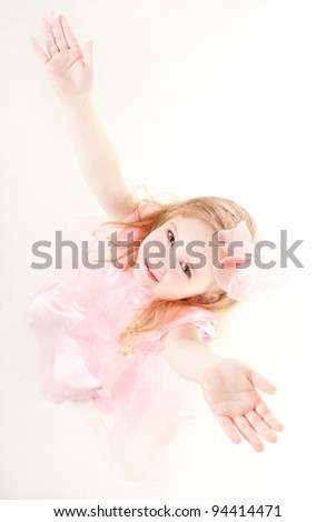 lovely little girl wearing pink dress  with her hands up - stock photo