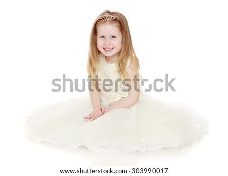 Lovely little girl with flowing blonde hair in a long Princess dress. Girl sitting on floor and smiling at the camera-Isolated on white background - stock photo