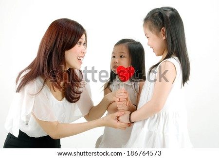 Lovely little girls giving a love shape to their mother on mothers day - stock photo