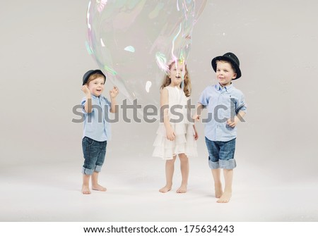 lovely little kids playing with soap bubbles - stock photo