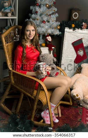 Lovely,long-haired,thinking,looking toward,holding a little,grey,nice teddy bear,cup of tea,coffee,milk,chocolate,red dress,sitting in the big wicker chair girl,winter,new-year's,christmas photostudio - stock photo