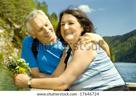 lovely mature couple beside a lake - stock photo