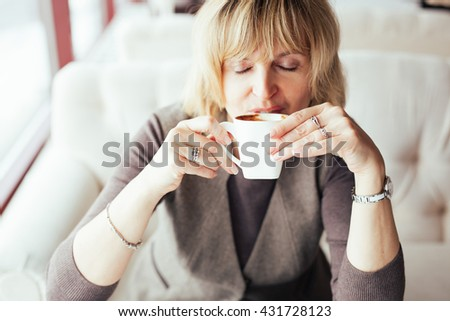 Lovely middle-aged blond woman with a beaming smile sitting in cafe having coffee - stock photo
