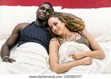 Lovely mixed race couple lying on bed. - stock photo