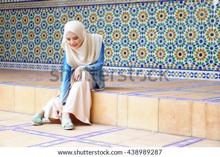 lovely muslim girl looking to her shoes and sitting in front of beautiful islamic pattern wall - stock photo