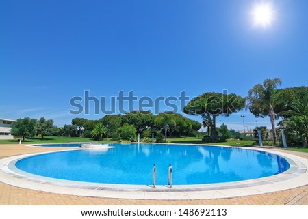 Lovely outdoor pool at the hotel for rest. - stock photo