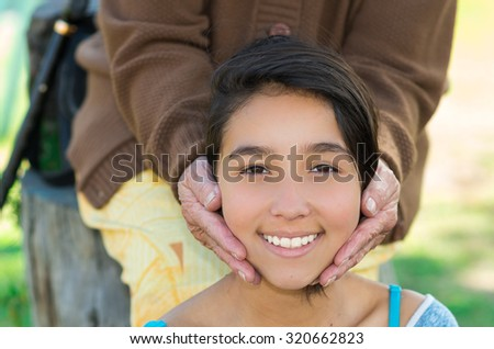 Lovely picture young girl headshot smiling naturally into camera with grandmothers hands holding her head. - stock photo
