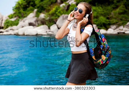 Lovely portrait of fresh beauty cute chick girl,hipster summer style outfit,aviator sunglasses,white big headphones,accessories casual,travel bag,fashionable street trendy outfit,summer vibe music - stock photo