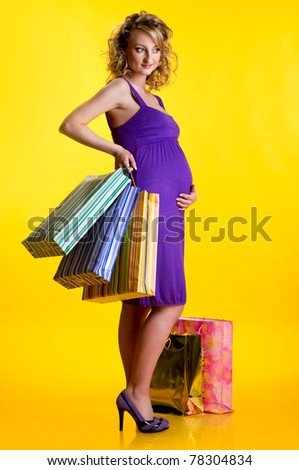 Lovely pregnant woman holding shopping bags isolated on yellow background - stock photo