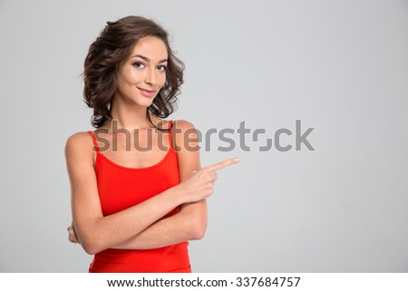 Lovely pretty young curly attractive woman in red top standing and pointing away in copyspace - stock photo
