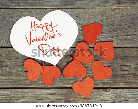 lovely red hearts - big white Heart hanging on the clothesline. Space for info text. On old wooden background. Romantic date, love Happy Valentines Day message. Toned image - stock photo