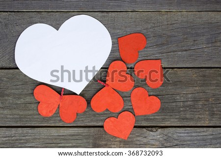 lovely red hearts - big white Heart hanging on the clothesline. Space for info text. On old wooden background. Romantic date, love Valentines Day concept. Toned image - stock photo