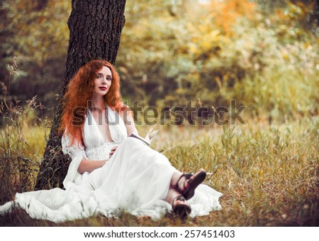 Lovely redhead woman sitting under the tree and reading a book - stock photo