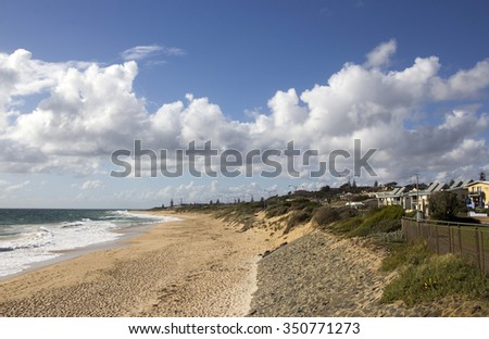 Lovely scenic view of Cumulo-nimbus clouds over  Ocean Beach Bunbury Western Australia on a stormy  late afternoon in autumn with waves breaking  on the wet sandy shore. - stock photo