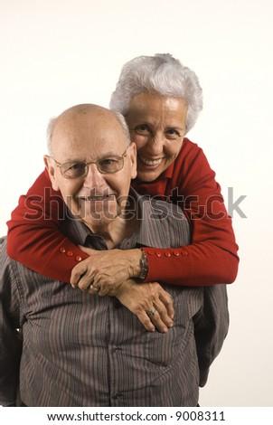 Lovely senior couple in piggyback ride - stock photo