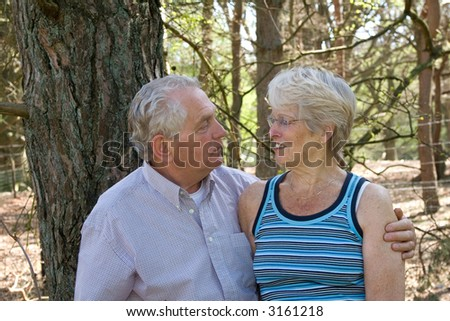 Lovely senior couple together on a sunny summer day out in the wood - stock photo