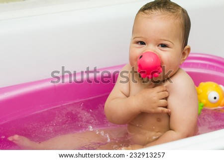 Lovely smiling baby fun in the bathroom with water toys  looking at the camera. - stock photo