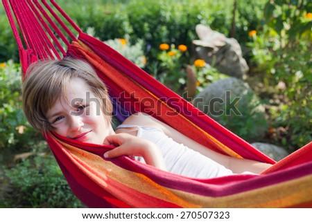 Lovely smiling girl relaxing in a hammock in a garden - stock photo