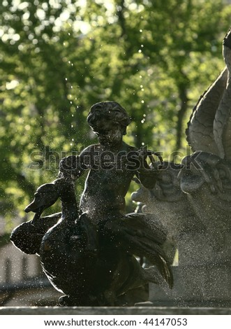 lovely sunlit fountain with an angel and drops of water in the air - stock photo