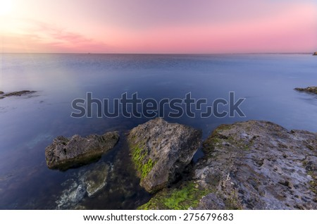 lovely sunset, overlooking the sharp rocky shore of the ocean. amazing seascape - stock photo