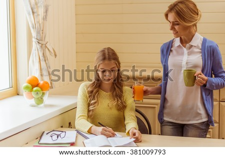 Lovely teenage girl doing a homework, beautiful mother holding a cup and giving her daughter a glass of juice. - stock photo