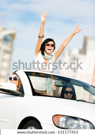Lovely teenager with her hands up in the car with friends. Girls ride somewhere on vacation - stock photo