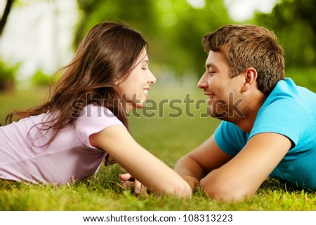Lovely valentines lying on the grass face to face and smiling to each other - stock photo