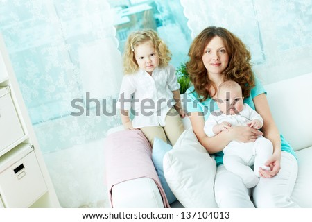 Lovely woman and her two infants sitting on sofa at home - stock photo