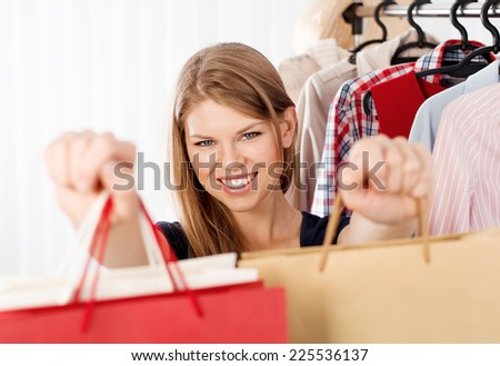 Lovely woman customer with shopping bags standing at clothing rack in retail store. Young pretty female clothes shop owner giving purchase to customer. - stock photo