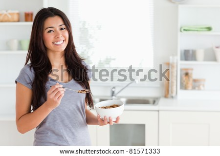 Lovely woman enjoying a bowl of cereal while standing in the kitchen - stock photo