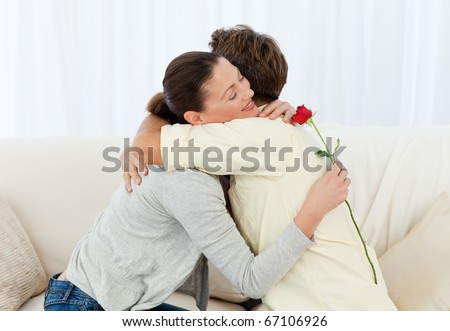 Lovely woman hugging his boyfriend after receiving a flower in the living room - stock photo